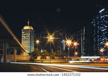 Night city Dubai with glowing light from the road and buildings near the metro station line