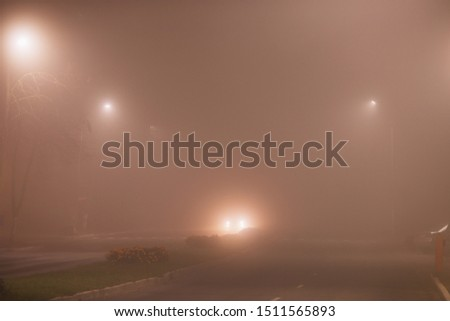 Night city in fog background. Thick mist in dark scary evening city. Dark creepy mystical city in dense fog. Spooky mist background. Darkness in city. Magic foggy landscape. Mysterious street;