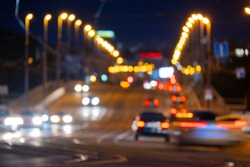 Night city in the evening with blurry headlights of cars, street lamps and the shine of tram rails.