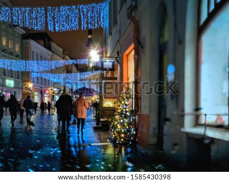 Night city lifestyle  rainy weather Tallinn panorama senior couple ,people walking on street ,blurred light , Estonia ,travelling   Christmas holiday in Europe ,cozy night urban landscape