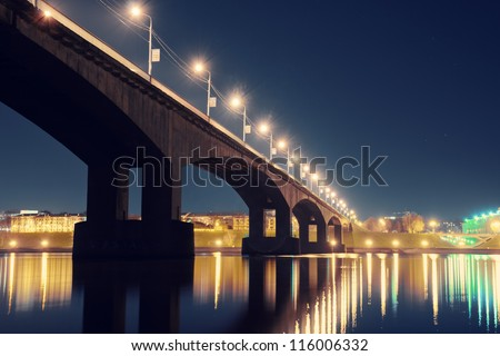 Night city lights reflected from surface of river in Russia with old bridge over Volga River