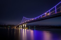 Night city minimal landscape. Dark and tranquil long exposure photography with led illuminated bridge and light reflections in the water. Pedestrian bridge across the Dnieper river, Kyiv, Ukraine