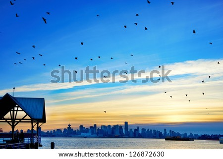 Night city, panoramic scene of downtown reflected in water. Sunset above Vancouver, Canada