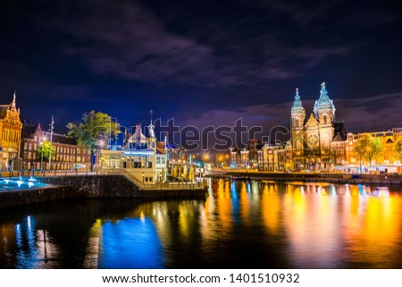 Night city view of Amsterdam canal and Basilica of Saint Nicholas, Holland, Netherlands.