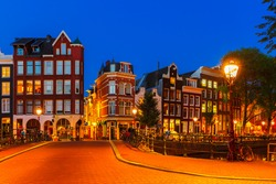Night city view of Amsterdam canal and bridge, typical dutch houses and bikes, Holland, Netherlands.