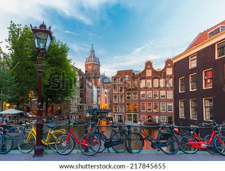 Night city view of Amsterdam canal, bridge and typical houses, Holland, Netherlands. Long exposure.