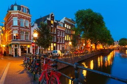 Night city view of Amsterdam canal, bridge with typical houses and bicycles, Holland, Netherlands.