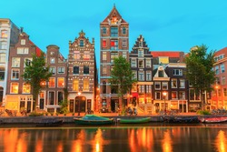 Night city view of Amsterdam canal Herengracht with typical dutch houses, boats and bicycles, Holland, Netherlands.