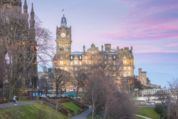 Night cityscape in Edinburgh, Scotland with colourful sunset or sunrise sky over the Balmoral Clock Tower, next to Princes Street Gardens, and above Waverley Station.