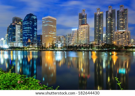Night cityscape, office buildings and apartments in Thailand at dusk. View from public park.