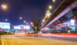 Night cityscape view with long traffic light trails at Sinakharin Toll Gate of Sirat Expressway. In Bangkok, Thaiand, Southeast Asia.