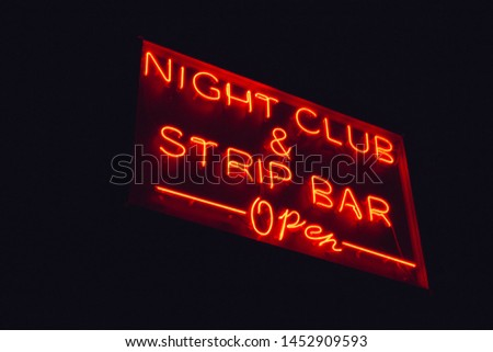 Night club and strip bar open red neon sign in the night
