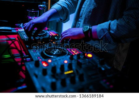Night club, nightlife concept. DJ hands hold microphone and mixing DJ remote. Neon light