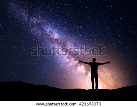 Night colorful landscape with Milky Way, yellow city lights and silhouette of a standing sporty man with raised up arms on the mountain. Universe. Travel background with purple sky full of stars