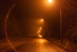 night desert two-lane road in the fog, along the road shine lanterns