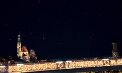 night European city Salzburg landmark long exposure photography urban view with fuzzy bridge yellow illumination lamps and church building dark star sky background space