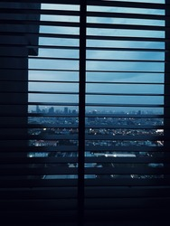 Night fall view of large window with Venetian blinds. View overlooking city skyscrapers and cloudy sky conveys sad, lonely and desperate feeling.