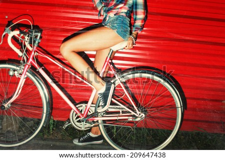 Night flash light picture of bicycle riding sexy girl in summer on red background urban style vintage bike