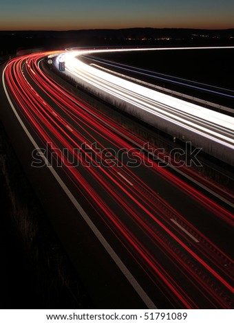Night highway (Cars in a rush moving fast on a highway  (speedway) in the UK at the nightfall