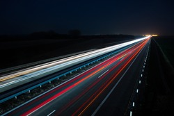 Night highway with car traffic and blurry lights when long exposure