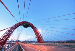 Night illuminated road through the suspended bridge with blue sky background