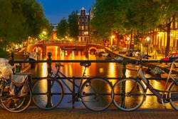 Night  illumination of Amsterdam canal and bridge with typical dutch houses, boats and bicycles, Holland, Netherlands.