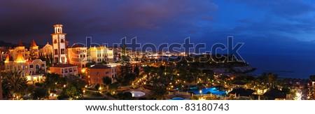 Night illumination of luxury hotel during sunset and Playa de las Americas at background, Tenerife island, Spain