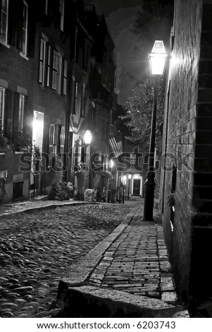 night image of an old 19th Century cobble stone road in Boston Massachusetts, lit only by the gas lamps revealing the shuttered windows and brightly lit doorways of the rowhouses on Acorn Street