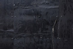 Night image of textures on a wall of black painted weathered plywood on a building worksite fence.