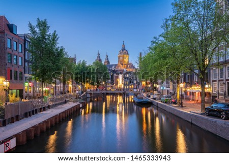 Night in Amsterdam city with Saint Nicholas Church at night in Amsterdam, Netherlands.