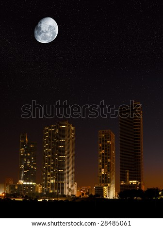 Night in the city - moon showing in the sky over skyscrapers