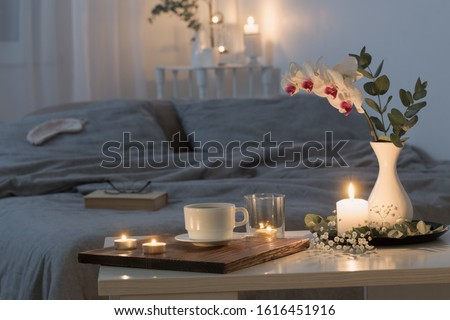 Photo of  night interior of bedroom with flowers and burning candles