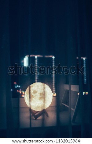 night lamp in the form of the full moon glows, stands on the windowsill behind the curtains on the background of the windows and lights of the night city #1132015964