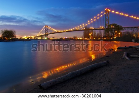 Night landscape. Ambassador Bridge linking Detroit, USA and Windsor ON, Canada. The second bridge, significantly larger is under construction. - stock photo
