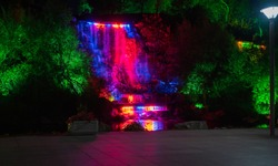 Night landscape, falling fountain with multi-colored paints a public park