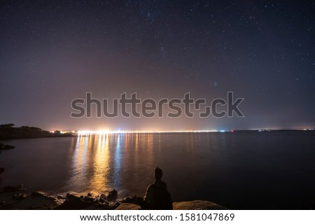 Night landscape from a cove on the outskirts of the urban center of s'Estanyol in Mallorca, starry night and light pollution, and a seated man silhouette contemplating the beauty of the night. Foto d'archivio ©