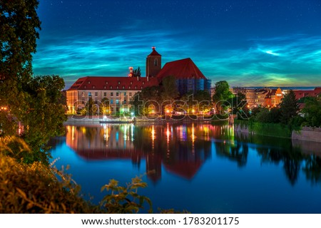 Night landscape noctilucent clouds (NLC) in the upper atmosphere of Earth above Wroclaw. Beautiful night shining clouds and stars over city historical landmarks and reflecting in the river at dusk ストックフォト ©