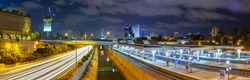 Night Landscape of TLV  from the bridge. Panoramic cityscape of Tel Aviv city at night with an intensive traffic on highway, central rail station, river and skyscrapers of  business center.