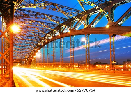 Night landscape with lights from cars on the background of metal structures bridge (speed)
