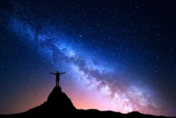 Night landscape with Milky Way. Silhouette of a standing man with raised up arms on the top of mountain. High rocks, mountain peak. Beautiful Galaxy.  Universe. Blue night starry sky and city lights