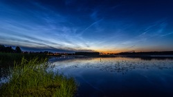 Night landscape with silver clouds (Noctilucent clouds) over the lake. Formed in the mesosphere. Rare atmospheric clouds that can only be seen at dusk and only in the temperate and polar latitudes.