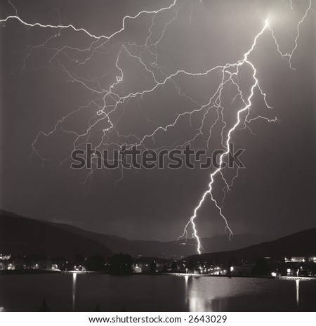 Night lightning storm near lake in mountains (B&W)