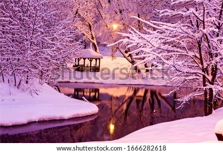 Night lights in winter park river snow scene. Gazebo in night winter forest park. Night forest park river view. Night lights in winter snow park