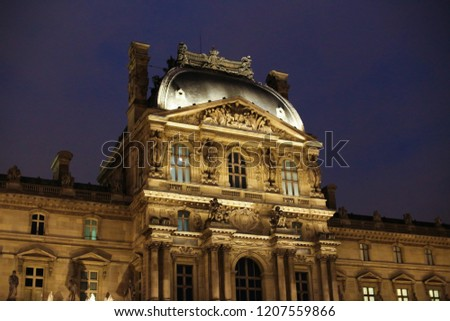 Night Louvre in dark blue sky background. Concept of French landmarks and trip to Paris.