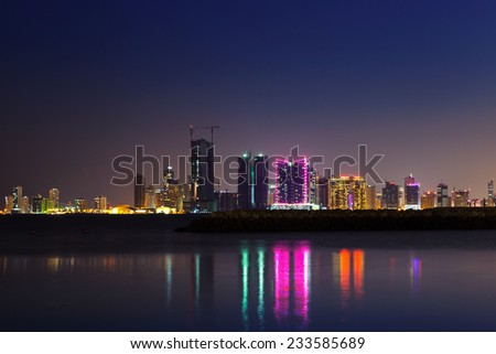Night modern city skyline with shining lights and reflections in the water. Manama, the Capital of Bahrain, Middle East #233585689