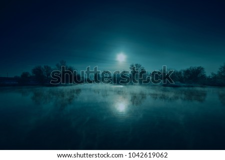 Night mystical scenery. Full moon over foggy river.