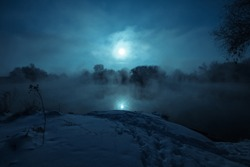 Night mystical scenery. Full moon over foggy river. Snow covered riverbank.