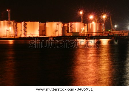Night oil tanks in the harbor with reflection on the sea