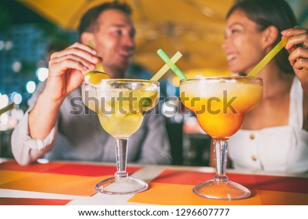 Night out drinking giant margaritas cocktails party couple going out at Miami Ocean drive restaurant having fun. Funny drinks at outdoor terrace young people travel lifestyle.