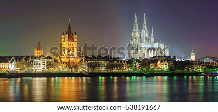 Night panorama of Cologne, Germany, with Cologne Cathedral, Great St. Martin Church, Colonius TV Tower and main train station reflecting in Rhine river